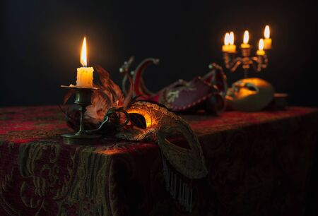 Burning candle in small brass candlestick and old carnival masks on a dark background, selective focus.
