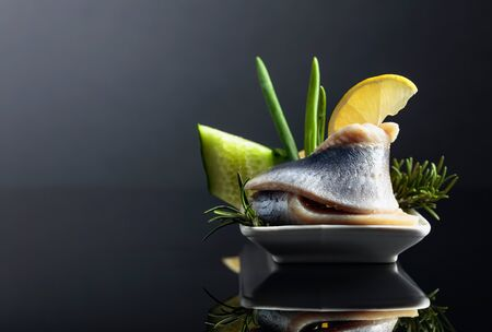 Atlantic herring with lemon, green cucumber, onion and rosemary. Copy space for your content.