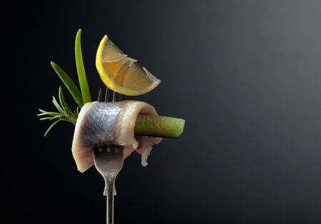 Atlantic herring with lemon, green cucumber, onion and rosemary. Herring fillet in oil on a fork. Copy space.