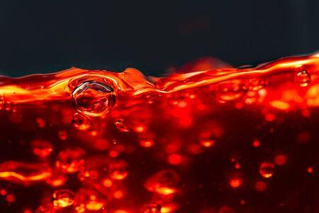 Alcoholic drink on dark background, abstract splashing. Macro shot. Stock Photo