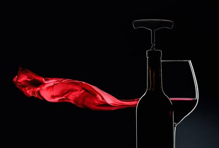 Bottle with corkscrew and glass of red wine on a dark background. Copy space. 스톡 콘텐츠