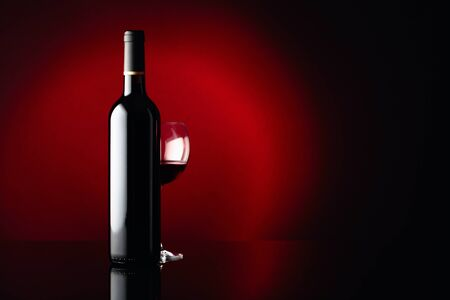 Glass and bottle of red wine on a black reflective background. Free space for your content. Standard-Bild