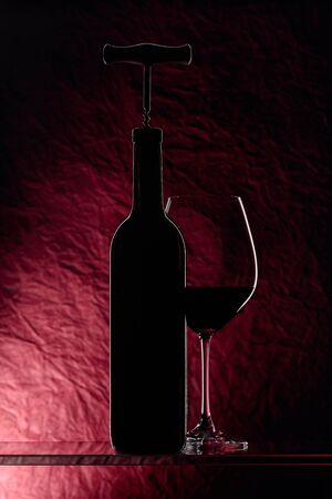 Bottle with corkscrew and glass of red wine on a dark red background. 스톡 콘텐츠