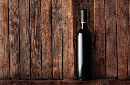 Bottle of red wine on a old wooden background. Free space for your content.