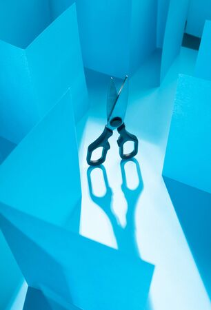 Scissors in blue paper labyrinth. Concept of theme of bureaucracy. Stock Photo