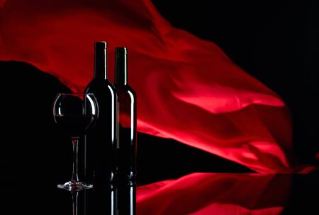 Wineglass and bottles of red wine on a black reflective background. Red satin curtain flutters in the wind. Copy space.