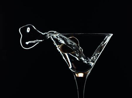 Splash de martini. Silueta de martini con aceitunas verdes sobre fondo negro. Foto de archivo