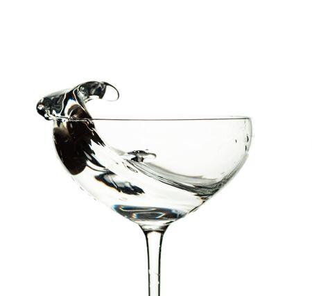 Martini and green olive in glass with splashes isolated on white background.