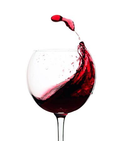 Chorrito de vino tinto en un vaso aislado sobre un fondo blanco. Foto de archivo