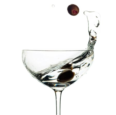 Martini and green olives in glass with splashes isolated on white background.