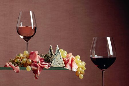 Grapes with blue cheese, prosciutto and thyme. Glasses of red and white wine with snacks. Copy space. Reklamní fotografie