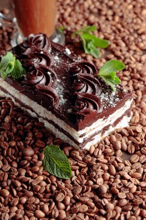 Delicious chocolate cake with mint. Coffee beans are scattered on the table.