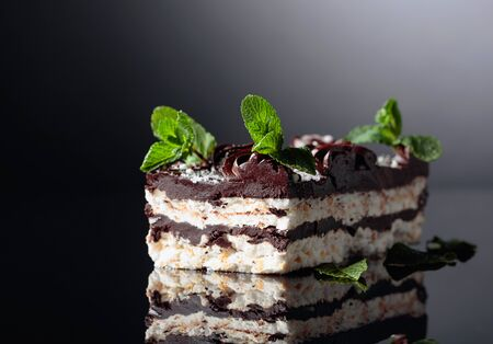 Delicious chocolate cake with mint on a black reflective background.  Copy space. 写真素材