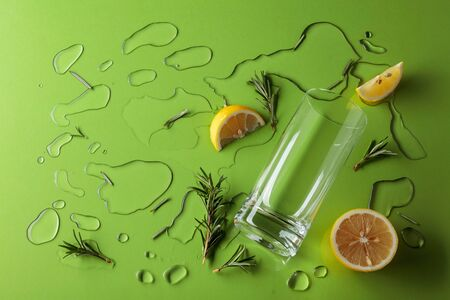 Cocktail gin-tonic with rosemary and lemon on a green background. Top view. Banque d'images