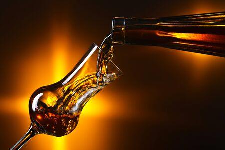 Starkes alkoholisches Getränk wird in ein Glas gegossen. Platz kopieren.