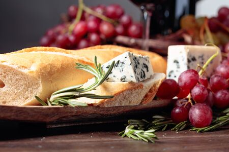 Bread with blue cheese and rosemary on a wooden table. Delicious snack and red wine. Copy space for your text.