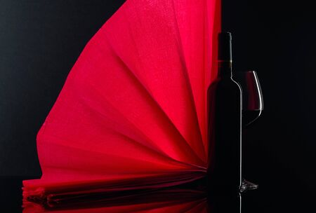 Closed bottle and glass of red wine on a black background. Free space for your content.