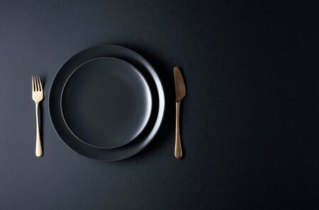 Empty black plate, fork and knife on a black background. Top view, copy space.