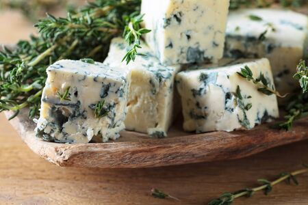 Pieces of blue cheese with thyme on a wooden table.