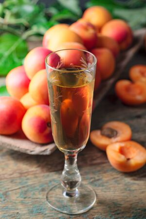 Apricot liqueur or wine and juicy fruits on a wooden table.
