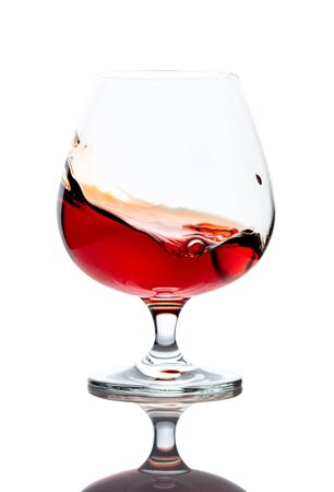 Splash of cognac in glass, isolated on white background. Stock Photo