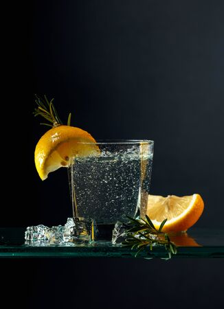 Cocktail gin-tonic with lemon and rosemary. Carbonated drink with ice pieces on a glass table. Black background, copy space.