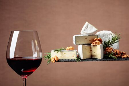 Red wine and soft cheeses with walnuts and rosemary. Copy space.