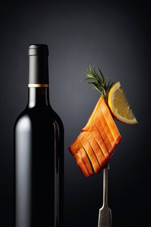 Bottle of wine and smoked squid with lemon slice.