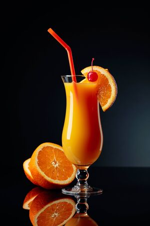 Tequila Sunrise cocktail with orange and cherry on a black reflective background.