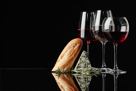 Blue cheese with bread, rosemary and wine on a black reflective background. Glasses with red, pink and white wine. Copy space for your text.