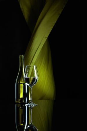 Wineglass and bottle of white wine on a black reflective background. Green satin curtain flutters in the wind. Copy space.