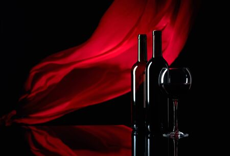 Wineglass and bottles of red wine on a black reflective background. Red satin curtain flutters in the wind. Focus on foreground. Copy space. 写真素材