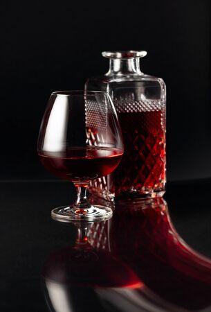 Glass of brandy and a carafe on a dark background. Fancy reflection on a black reflexive background. Reklamní fotografie