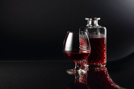 Glass of brandy and a carafe on a dark background. Fancy reflection on a black reflexive background. Copy space.