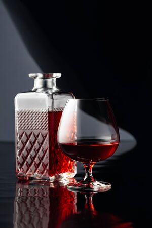 Decanter and glass of brandy on a black reflective background.