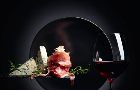 Glass of red wine with traditional mediterranean snacks. Prosciutto or spanish jamon with blue cheese and rosemary. Stock Photo