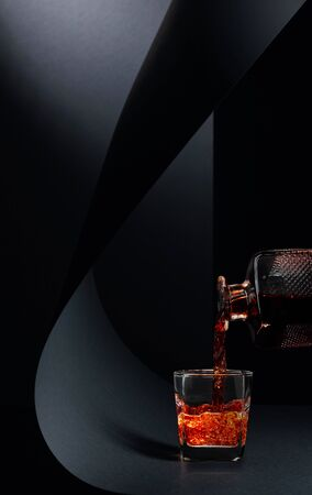 Glass of whiskey on a black background. Copy space.
