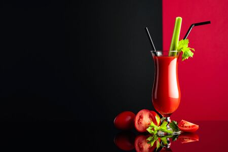 Glass of tomato juice with celery and fresh tomatoes on a black reflective background. Copy space.