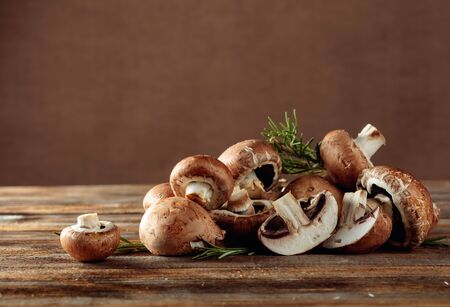 Fresh brown mushrooms champignon on a old wooden table. Copy space.