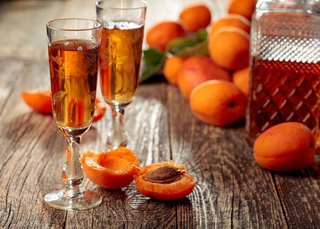 Apricot liquor and fresh apricots on a old wooden table. Wine and juicy fruits on a rustic background.