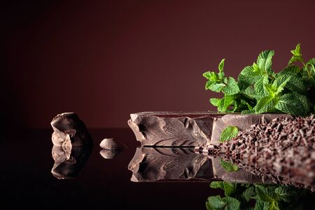 Pieces of dark bitter chocolate and chocolate chips with mint on a black reflective background. Copy space.