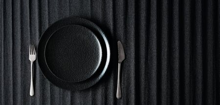 Empty black plate, fork and knife on a black background. Top view, copy space. Фото со стока