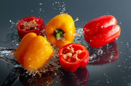 Red and yellow paprika in water splashes on a black background.