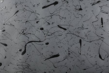 Black matte background with splashes and drops of glossy black paint.