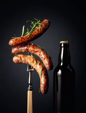 Bottle of beer and grilled Bavarian sausages with rosemary. Sausages on a fork sprinkled with rosemary. Stock Photo