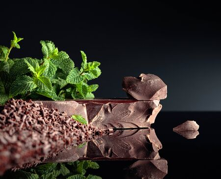 Pieces of dark bitter chocolate, chocolate chips and mint on a black reflective background.