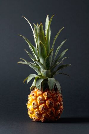 Ripe and juicy pineapple on a black background.