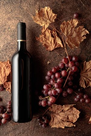 Bottle of red wine with ripe grapes and dried up vine leaves. Old copper background.  Copy space, top view. Standard-Bild