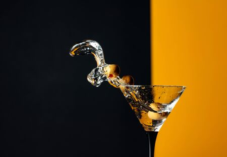 Martini with green olives. Splash on a black background. Copy space. Foto de archivo