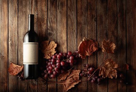 Bottle of red wine with ripe grapes and dried up vine leaves. Old wooden background. On a bottle old empty label. Copy space, top view.